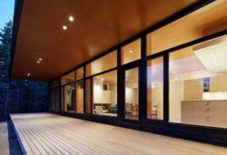 Terrasse bois et grande baie vitrée vue salon - Lockeport-Beach-House par Nova Tayona Architects - Nouvelle-Ecosse, Canada © Janet Kimber
