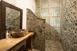 Salle de bains avec façade bouteilles recyclées - Earthship Te Timatanga par Gus-Sarah - Waikato, Nouvelle-Zelande