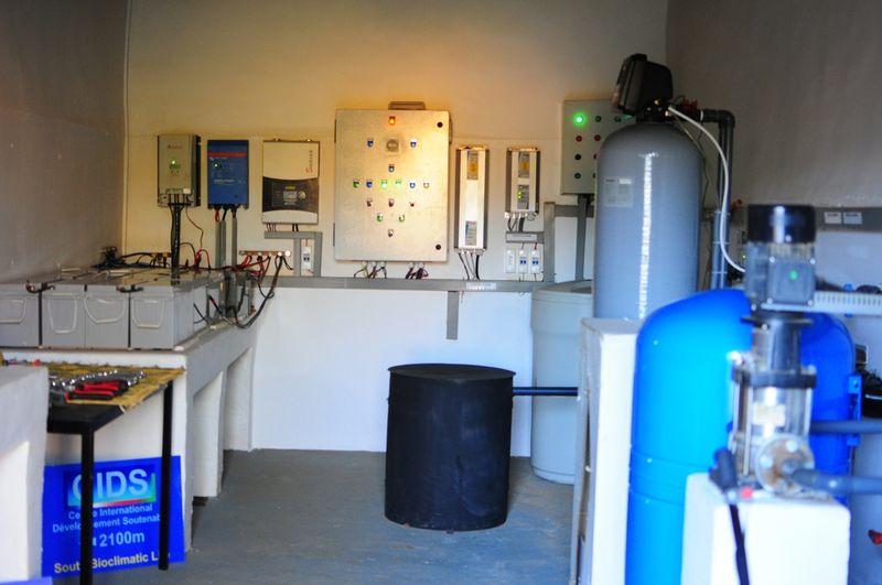 local technique avec à gauche les batteries, au centre la tête du forage et à droite le traitement de l'eau