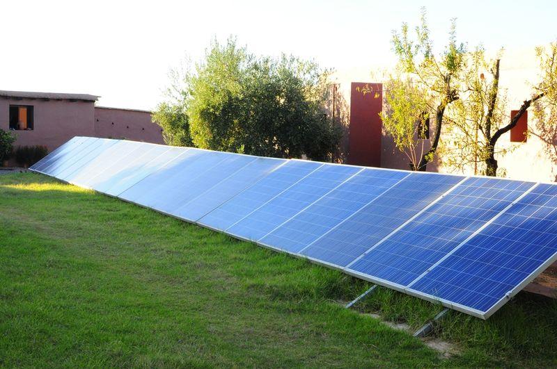 panneaux photovoltaïques posés au sol pour faciliter leur entretien, mais aussi leur arrosage et bénéficier de l'évapo-transpiration du gazon
